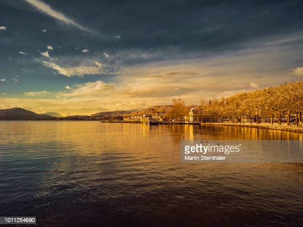 sonnenuntergang am wörthersee promenade in der ostbucht - sonnenuntergang stock pictures, royalty-free photos & images