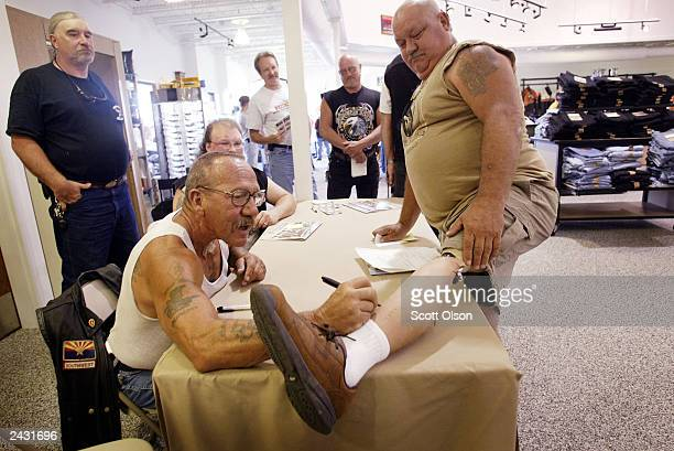 Sonny Barger founder of the Oakland California charter of the Hells Angels motorcycle club autographs the artificial leg of Kenny Little during an...