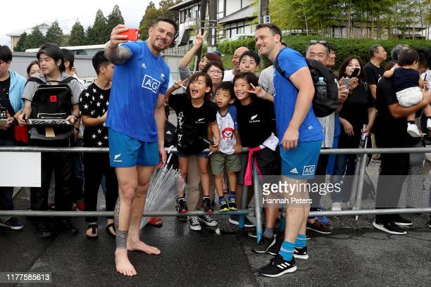 Sonny Bill Williams and Ben Smith of the All Blacks pose with fans following a New Zealand training session at Jissoji Tamokuteki Ground on September...