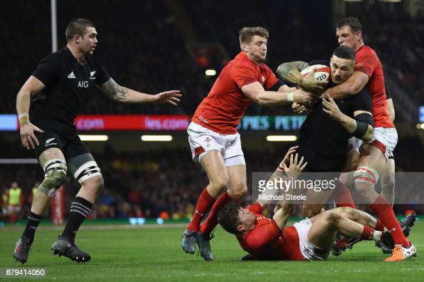 Sonny Bill Williams of New Zealand is held up by Dan Biggar Aaron Shingler and Steff Evans of Wales during the International match between Wales and...