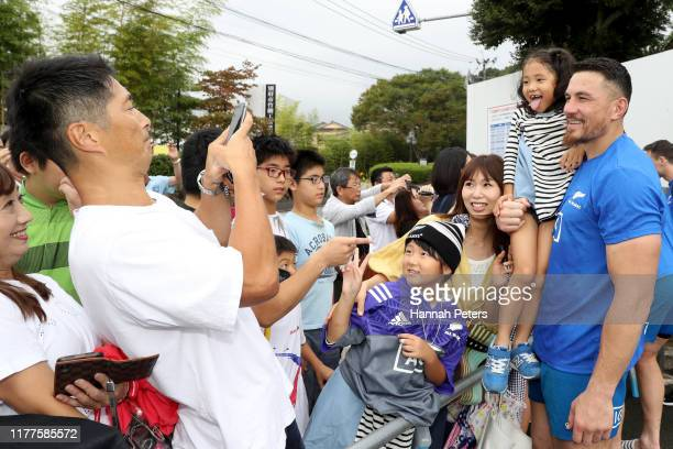 Sonny Bill Williams of the All Blacks poses with fans following a New Zealand training session at Jissoji Tamokuteki Ground on September 28, 2019 in...