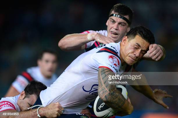 Sonny BillWilliams is tackled by Ethan Lowe and Kane Linnett of the Cowboys during the round 10 NRL match between the North Queensland Cowboys and...