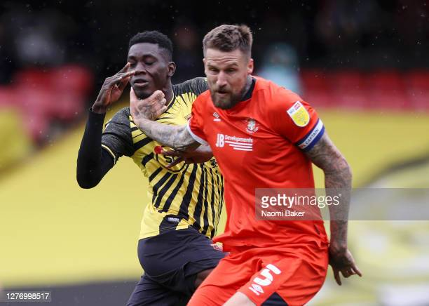 Sonny Bradley of Luton Town is seen with his hands on Ismaila Sarr of Watford's throat during a challenge during the Sky Bet Championship match...