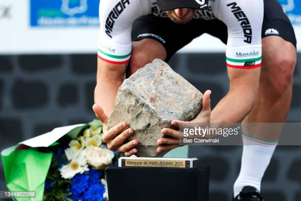 Sonny Colbrelli of Italy and Team Bahrain Victorious celebrates winning the race and holds his cobblestone trophy on the podium ceremony after the...