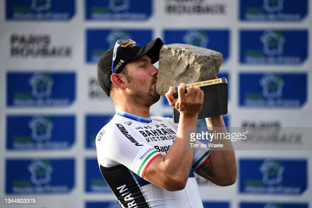 Sonny Colbrelli of Italy and Team Bahrain Victorious celebrates winning the race and kisses his cobblestone trophy on the podium ceremony after the...