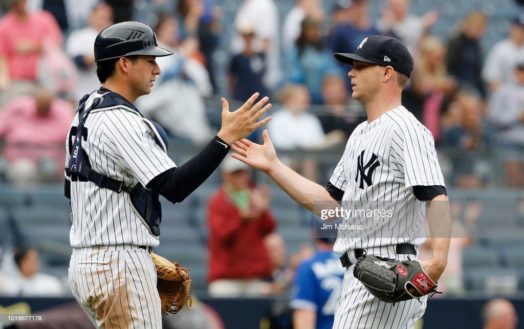 Sonny Gray #55 and Kyle Higashioka #66 of the New York Yankees celebrate after defeating the Toronto Blue Jays at Yankee Stadium on August 19, 2018 in the Bronx borough of New York City.