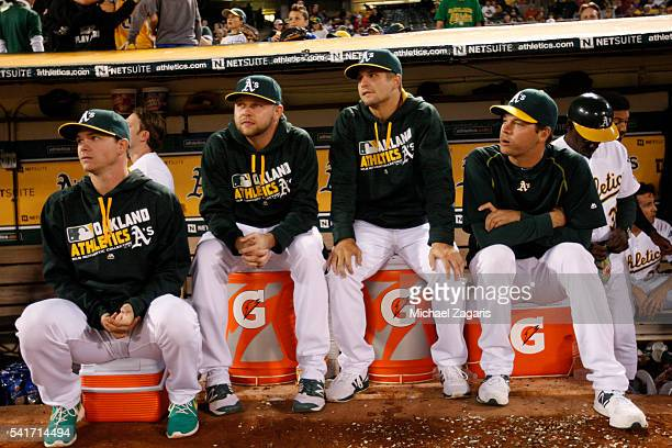 Sonny Gray Jesse Hahn Kendall Graveman and Rich Hill of the Oakland Athletics sit in the dugout during the game against the Minnesota Twins at the...