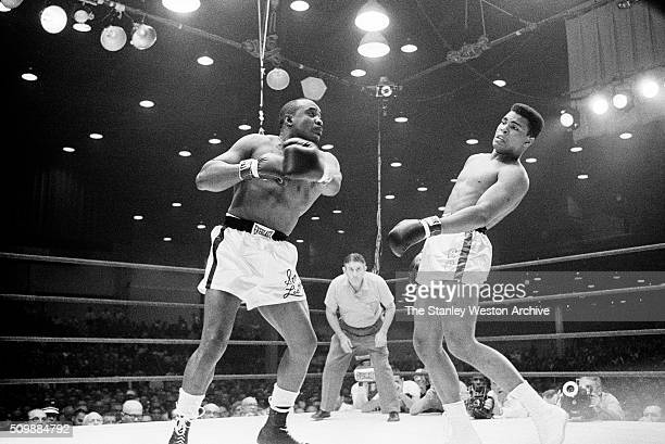 Sonny Liston throws a punch against Cassius Clay who slipps the punch during their bout at the Convention Center in Miami Beach Florida February 25...