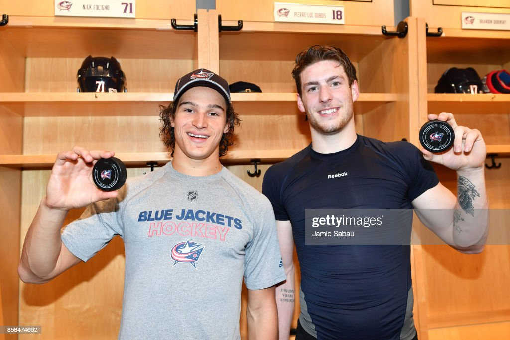 Sonny Milano #22 and Pierre-Luc Dubois #18 of the Columbus Blue Jackets hold the pucks from their first career NHL goals scored during a game against the New York Islanders on October 6, 2017 at Nationwide Arena in Columbus, Ohio. Columbus shutout New York 5-0.