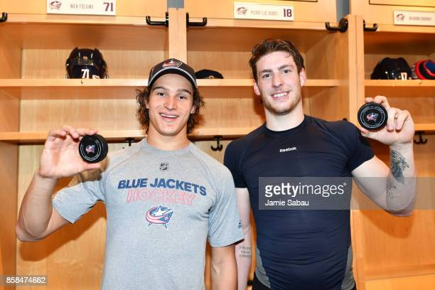 Sonny Milano and PierreLuc Dubois of the Columbus Blue Jackets hold the pucks from their first career NHL goals scored during a game against the New...