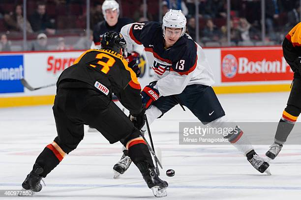 Sonny Milano of Team United States tries to get the puck past Tim Bender of Team Germany during the 2015 IIHF World Junior Hockey Championship game...