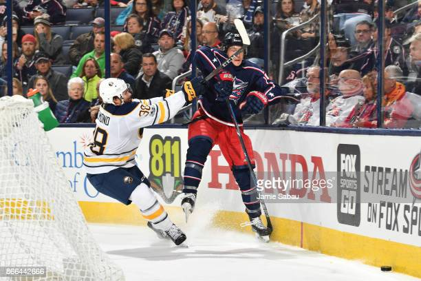 Sonny Milano of the Columbus Blue Jackets is checked by Zach Redmond of the Buffalo Sabres after clearing the puck during the third period of a game...