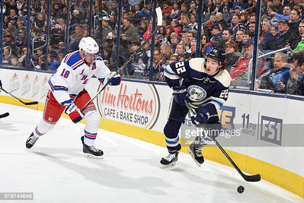 Sonny Milano of the Columbus Blue Jackets looks up ice as he skates the puck away from Marc Staal of the New York Rangers during the first period of...