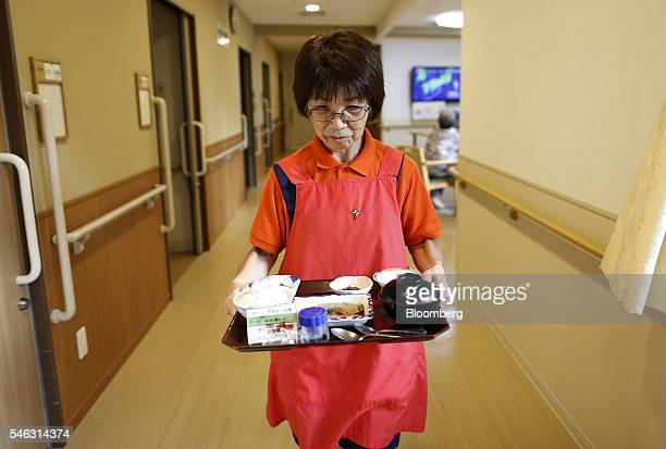 Sonoe Kudo 65 year old caregiver carries dinner to a resident at a nursing home operated by Care Twentyone Corp in Kasai Tokyo Japan on Thursday June...