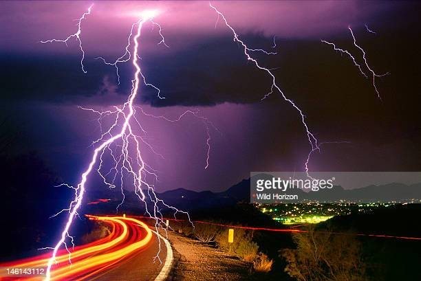Sonoran Desert rainstorm a summer monsoon thunderstorm with cloudtoground lightning strikes and light trails from cars on roadway This image was...