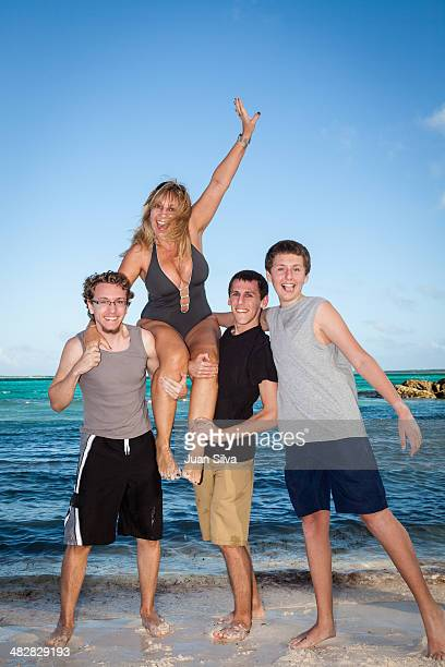 Sons carrying mother on shoulder on the beach