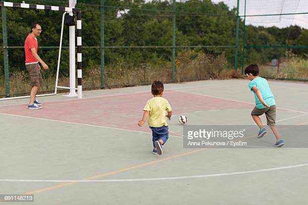 Sons Playing Soccer With Father On Court