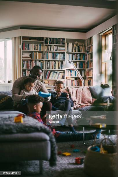 sons using smart phone while father with digital tablet sitting in living room - digital tablet stock pictures, royalty-free photos & images