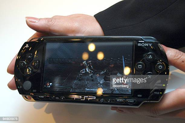 Sony Computer Entertainment employee holds the new Sony PSP at an unveiling in Tokyo Monday July 12 2004 Sales of Sony Corp's first handheld game...