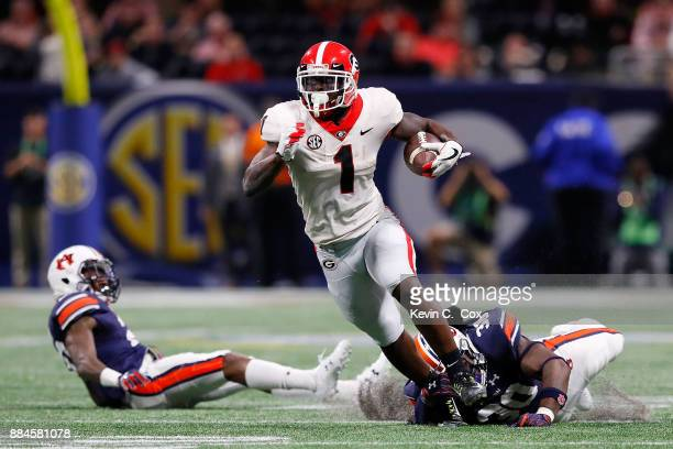 Sony Michel of the Georgia Bulldogs is avoids a tackle by Tre' Williams of the Auburn Tigers during the first half in the SEC Championship at...