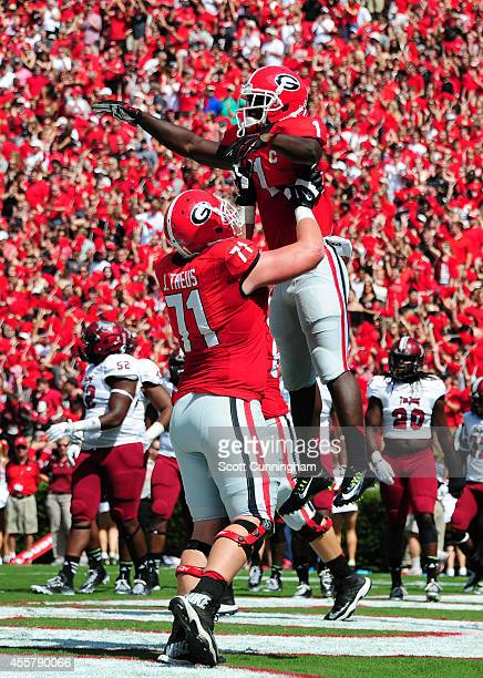 Sony Michel of the Georgia Bulldogs is hoisted by John Theus after scoring a first quarter touchdown against the Troy Trojans at Sanford Stadium on...