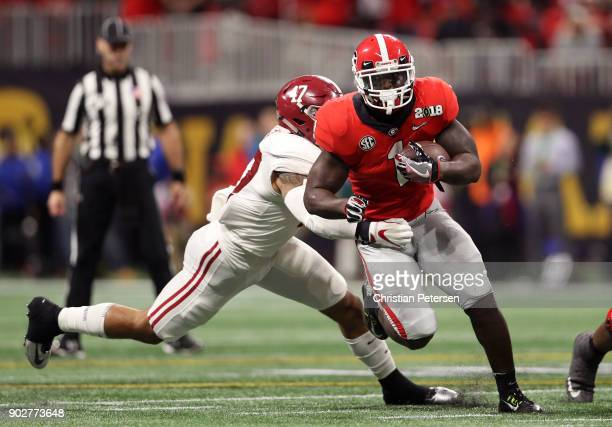 Sony Michel of the Georgia Bulldogs is tackled by Christian Miller of the Alabama Crimson Tide during the second half in the CFP National...