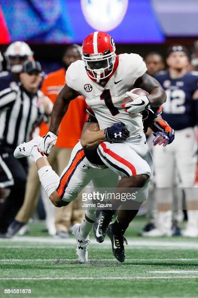 Sony Michel of the Georgia Bulldogs is tackled by Tray Matthews of the Auburn Tigers during the first half in the SEC Championship at MercedesBenz...