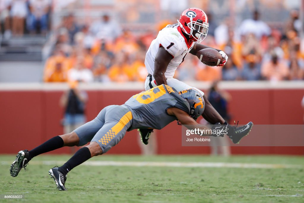 Sony Michel #1 of the Georgia Bulldogs runs the ball against Nigel Warrior #18 of the Tennessee Volunteers in the third quarter of a game at Neyland Stadium on September 30, 2017 in Knoxville, Tennessee. Georgia won 41-0.