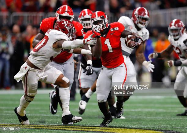 Sony Michel of the Georgia Bulldogs runs the ball away from Mack Wilson of the Alabama Crimson Tide during the second quarter in the CFP National...