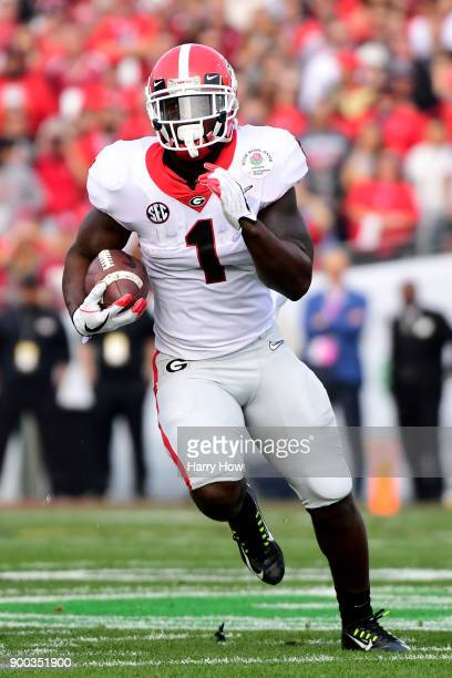 Sony Michel of the Georgia Bulldogs runs the ball down field for extra yardage in the 2018 College Football Playoff Semifinal Game against the...