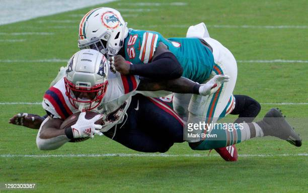 Sony Michel of the New England Patriots is tackled by Jerome Baker of the Miami Dolphins during the fourth quarter in the game at Hard Rock Stadium...