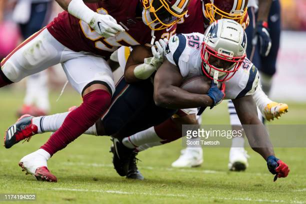 Sony Michel of the New England Patriots is tackled by Quinton Dunbar and Montae Nicholson of the Washington Redskins during the second half at...