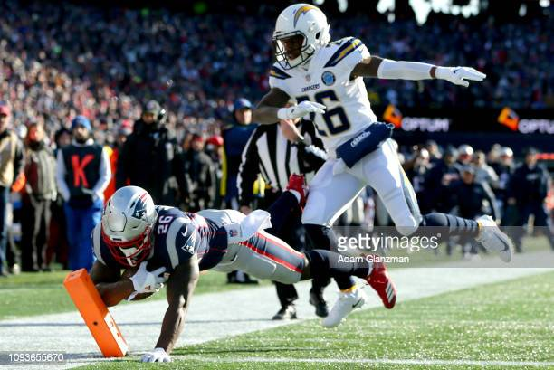 Sony Michel of the New England Patriots scores a touchdown as he is defended by Casey Hayward of the Los Angeles Chargers during the first quarter of...