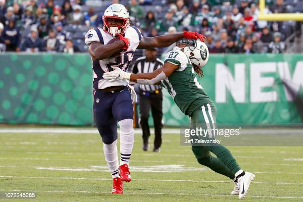 Sony Michel of the New England Patriots stiff arms Darryl Roberts of the New York Jets during the second half at MetLife Stadium on November 25 2018...
