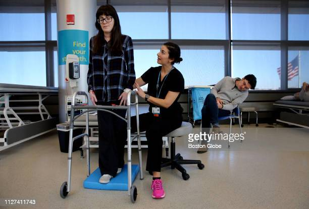 Sonya Bandouil left works on her balance with Doctor Rachel Benjamin while her boyfriend Alex Pankiewicz watches during physical therapy at Spaulding...