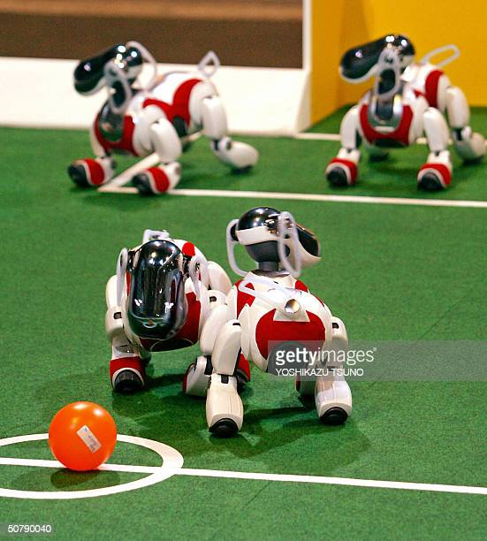 Sony's pet robots AIBO kicks off the ball to play soccer game during the fourleg league of the RoboCup Japan Open 2004 robots' soccer games in Osaka...