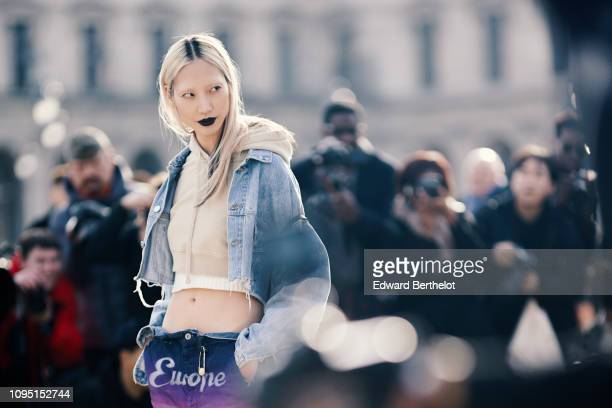 Soo Joo Park wears a blue denim jacket a cropped hoodie sweater a white cropped top purple 'Europe' pants poses in front of photographers outside...