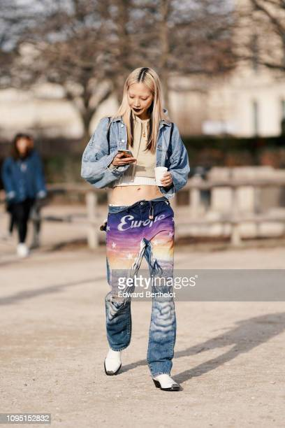 Soo Joo Park wears a blue denim jacket a cropped hoodie sweater a white cropped top purple 'Europe' pants outside OffWhite during Paris Fashion Week...
