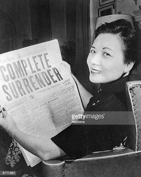 Soong MeiLing wife of Generalissimo Chiang KaiShek the Chinese nationalist leader looking over the victory headlines after the surrender of Japan in...