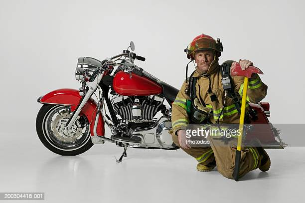 Sooty fireman with axe in full uniform sitting by large red motorbike in studio, portrait