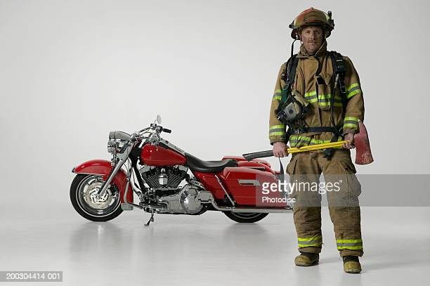 Sooty fireman with axe in full uniform standing by large red motorbike in studio, portrait