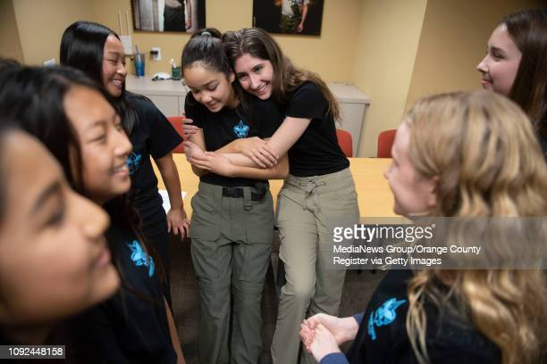 Sophia Del Rosario center left gets a hug from Jennaele Beau after a ceremony at Boy Scouts of America's Orange County headquarters in Costa Mesa on...