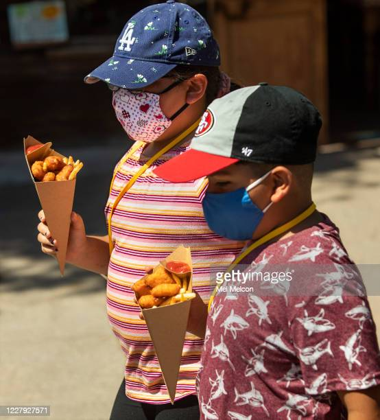 Sophia Dominguez left and her brother Nathan of La Puente make their way with mac and cheese bites with french fries during Knotts Tase of Calico...