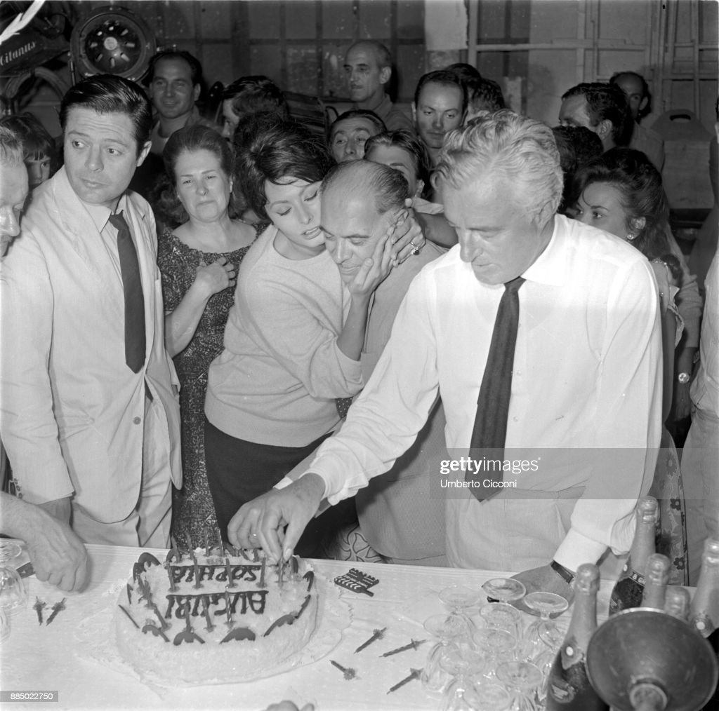 Sophia Loren hugs film producer Carlo Ponti during her twenty-ninth birthday party, Marcello Mastroianni (left) and Vittorio De Sica (right) are attending the party too, Italy 1963.