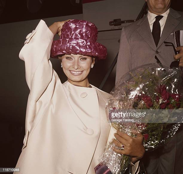 Sophia Loren Italian actress holding onto her hat while carrying a bouquet of flowers on her arrival at London Airport London England Great Britain...