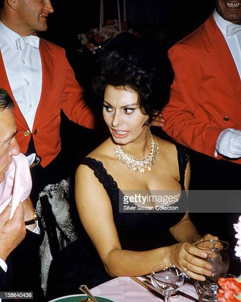 Sophia Loren Italian actress wearing a sleeveless black dress with a diamond necklace as she turns to speak to the person beside her circa 1960
