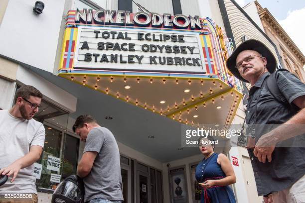 People walk by the Nickelodeon Theater August 20 2017 in Columbia South Carolina COLUMBIA SC AUGUST 20 Sophia Neghesti sells eclipse glasses on Main...