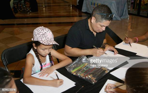 Sophia Ramirez and her father artist John Ramirez draw during a preview event at the Magical Memories Fine Art Gallery inside The Forum Shops At...