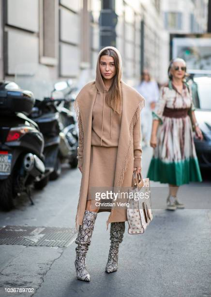 Sophia Roe wearing beige hoody skirt and coat snake print boots is seen outside Max Mara during Milan Fashion Week Spring/Summer 2019 on September 20...