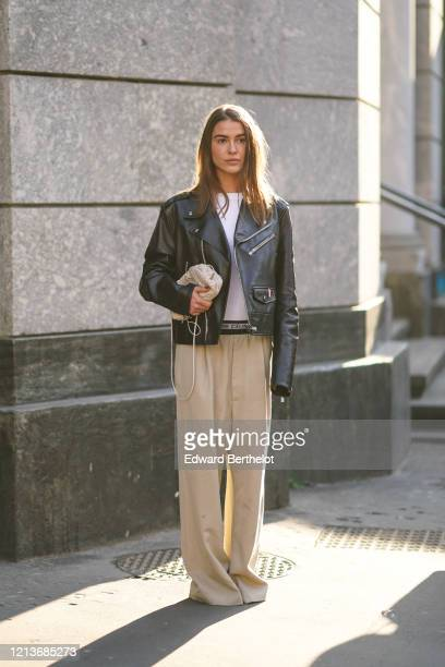 Sophia Roe wears a white top, a black leather biker jacket, beige wide-legs full-length pleated pants, a beige woven leather bag, outside Philosophy,...